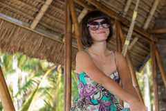 Красивая счастливая молодая женщина в солнечных очках сидя в деревянном газебо на солнечном дне Тропический остров Бали, Индонези Стоковое Изображение RF