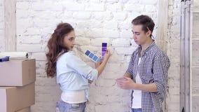 Красивая счастливая молодая семья стоя против стены выбирает цвет образцов акции видеоматериалы