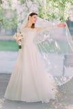 Красивая счастливая невеста закручивая вокруг при вуаль держа bridal букет стоковое фото rf
