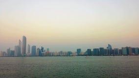 Красивая съемка горизонта города Абу-Даби возвышается и пляж на заходе солнца видеоматериал