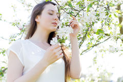 Красивая сладостная девушка в белой рубашке с зацветая яблонями в саде идет яркий теплый летний день Стоковые Изображения