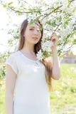 Красивая сладостная девушка в белой рубашке с зацветая яблонями в саде идет яркий теплый летний день Стоковое фото RF