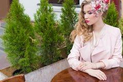 Красивая сладостная девушка с волосами и состав красят яркое усаживание на таблице на внешнем кафе и ждать ваш заказ Стоковое фото RF