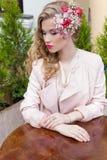 Красивая сладостная девушка с волосами и состав красят яркое усаживание на таблице на внешнем кафе и ждать ваш заказ Стоковые Фото