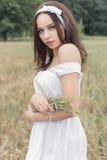 Красивая сладостная девушка с темными волосами в sundress белых платья лета идя в поле с колосками с белой лентой в ей Стоковое Изображение
