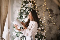 Красивая темн-с волосами девушка одетая в белых стойках свитера и брюк рядом с окном на предпосылке нового стоковые изображения