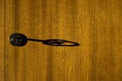 Красивая тень ключа в keyhole на деревянной двери Стоковое Изображение