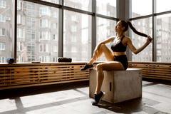 Красивая тонкая девушка одетая в черных спорт верхних и шортах сидит на деревянной коробке в солнечном свете во фронте стоковые изображения rf