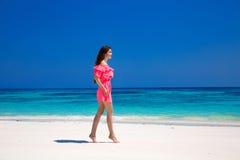Красивая тонкая женщина в красном платье наслаждаясь на экзотическом море, тропике Стоковая Фотография