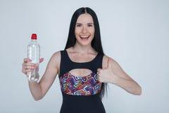 Красивая тонкая маленькая девочка брюнета резвится одежды на серой предпосылке Sporty здоровая модель держа бутылку воды и шоу стоковое фото rf