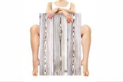 Красивая тонкая молодая женщина, сидя за частью ламината стоковая фотография rf