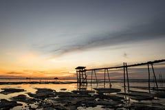 Красивая тропическая предпосылка захода солнца, деревянная башня водяной помпы на тинном пляже Стоковые Фотографии RF