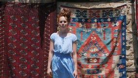 Красивая туристская девушка представляя на улице перед старыми восточными восточными коврами видеоматериал
