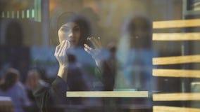 Красивая уверенная мусульманская женщина прикладывая косметики, сидя в кафе, кокетка сток-видео
