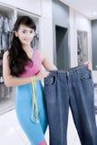 Красивая уменьшая женщина показывая ей старые джинсы стоковое фото