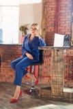 Красивая умная бизнес-леди сидя на таблице на рабочем месте с ноутбуко стоковое фото