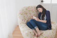 Красивая унылая девушка сидя на софе живущей комнаты Стоковое Изображение