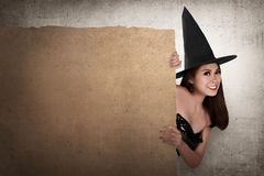 Красивая усмехаясь азиатская женщина с шляпой в владении костюма ведьмы Стоковые Изображения RF