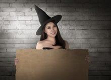 Красивая усмехаясь азиатская женщина с шляпой в владении костюма ведьмы Стоковое Изображение