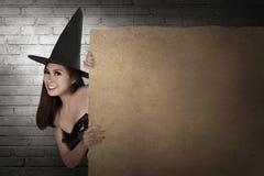 Красивая усмехаясь азиатская женщина с шляпой в владении костюма ведьмы Стоковое Фото