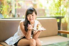 Красивая усмехаясь азиатская молодая женщина сидя на софе стоковое фото