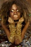 Красивая усмехаясь Афро-американская женщина в аксессуарах золота с оружиями пересекла под ее подбородок на яркой предпосылке Стоковые Изображения