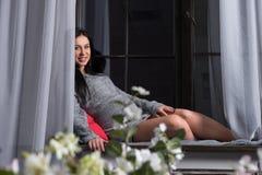 Красивая усмехаясь беременная женщина брюнет в связанном платье сидит Стоковые Фото