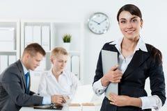 Красивая усмехаясь бизнес-леди в костюме держа доску сзажимом для бумаги в ha Стоковая Фотография
