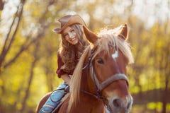 Красивая усмехаясь верховая лошадь девушки на поле осени Стоковая Фотография