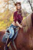Красивая усмехаясь верховая лошадь девушки на поле осени Стоковые Изображения RF