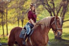 Красивая усмехаясь верховая лошадь девушки на поле осени Стоковые Изображения