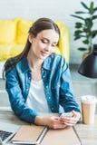 красивая усмехаясь девушка используя смартфон пока сидящ на столе и изучать стоковое фото rf