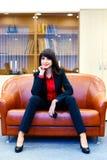 Красивая усмехаясь девушка в костюме сидя в офисе на cou Стоковые Изображения