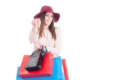 Красивая усмехаясь девушка с хозяйственными сумками указывая палец стоковое фото