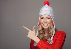Красивая усмехаясь женщина в одежде зимы Указывать на copyspace стоковое изображение