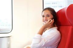 Красивая усмехаясь женщина говоря на умном телефоне в поезде Стоковая Фотография RF