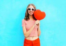 Красивая усмехаясь женщина держа в форме сердца воздушного шара руки красной над синью Стоковое Изображение