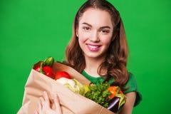 Красивая усмехаясь женщина держа продуктовую сумку полный Стоковое Изображение