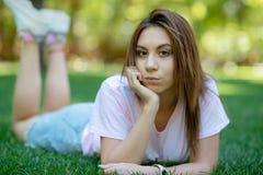 Красивая усмехаясь женщина лежа на траве внешней стоковые фотографии rf