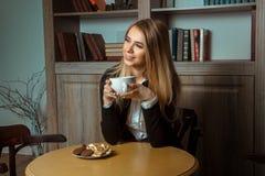 Красивая усмехаясь женщина на таблице с чашкой в его руках Стоковое Изображение
