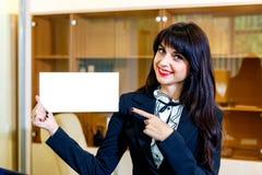 Красивая усмехаясь женщина показывает пустую карточку в офисе Стоковые Изображения RF