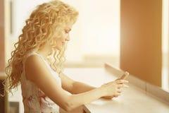 Красивая усмехаясь женщина посылая текст от ее мобильного телефона стоковая фотография rf