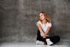 Красивая усмехаясь женщина сидя на поле против бетонной стены стоковая фотография