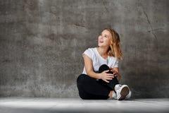 Красивая усмехаясь женщина сидя на поле против бетонной стены стоковые фотографии rf