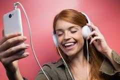 Красивая усмехаясь женщина слушая музыку с наушниками над розовой предпосылкой стоковые фотографии rf