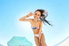 Красивая усмехаясь женщина смотрит внутри шатра и показывает что победа подписывает внутри камеру взгляд изнутри шатра на песочно Стоковая Фотография RF