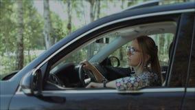 Красивая усмехаясь женщина смотря вне окно автомобиля сток-видео
