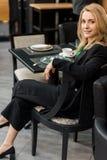 красивая усмехаясь женщина смотря камеру пока сидящ на таблице стоковое изображение