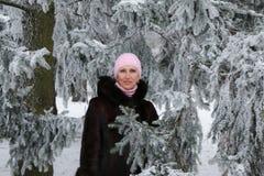 Красивая усмехаясь женщина среди покрытых снег деревьев стоковое фото