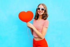 Красивая усмехаясь женщина с красной формой сердца воздушного шара над синью Стоковые Фотографии RF
